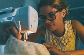 foto of sewing  - Young dressmaker sewing late at night at office - JPG