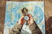 image of pov  - Traveler woman searching direction with a compass on background of map outdoor - JPG