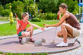 picture of miniature golf  - Family playing miniature golf in summer - JPG