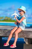 stock photo of girl toy  - Adorable little girl with toy airplane in hands on white beach - JPG