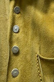 pic of buckskin  - A close up photo of an antique buckskin leather coat with unique elk horn buttons - JPG