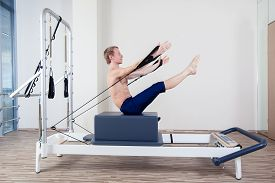 pic of pilates  - Pilates reformer workout exercises man at gym indoor - JPG
