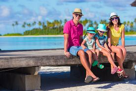 picture of four  - Beautiful family of four on beach during summer vacation - JPG