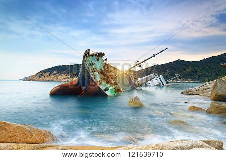 shipwreck or wrecked cargo ship abandoned on sea bay