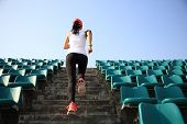 Runner athlete running on stairs. woman fitness jogging workout wellness concept. poster