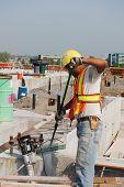 Tradesman cleans concrete pad on construction site
