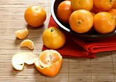 image of satsuma  - satsuma oranges in a wooden bowl presented on wooden bamboo mat - JPG