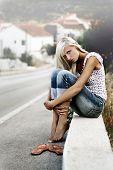 Jovem loira sentando-se pela estrada