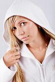 Blond swarthy woman wearing white fleece hoodie posing at studio