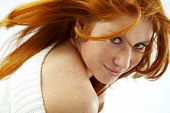 Sexy girl with red hair and freckles posing on white studio background