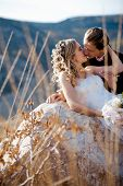 Kissing wedding couple on a stone outdoors