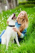Beautiful woman with her labrador on fresh green meadow