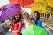 Three fashion teenage girls posing with colorful umbrellas in autumn park