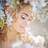 Portrait of beautiful blond bride in spring blossom
