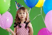 Child celebrating birthday on green studio background