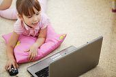 Little cute child working with laptop at home