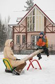 Mother With Son On Winter Seesaw