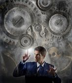 stock photo of mechanical engineer  - business man moving gear of big mechanism - JPG
