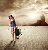girl with suitcase walking in a desert and leaving a city