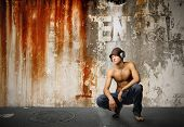 cool looking guy listening music with grunge wall on the background