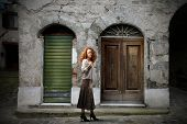 Red haired woman standing on a street before an ancient building