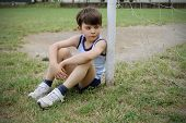 Sad child sitting against a football door