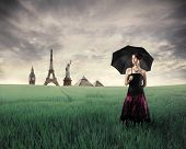 Beautiful woman with umbrella standing on a green meadow with landmarks from different cities on the background
