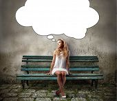 image of sitting a bench  - Young woman sitting on a park bench and thinking - JPG