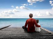 Father and son sitting on a wharf over the sea