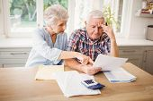 Worried senior couple checking their bills at home poster