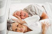 Senior woman covering her ears while man snoring in bed poster