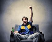 Sport fanatic sitting on an armchair and exulting