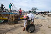 BALI - JANUARY 16: Life in a fishing village, womenfolk scavenges for ditched fish on the beach at J
