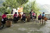 GUILIN, CHINA - MAY 23: Farm womenfolk work on clothes embroidery in front of their home in Longji o