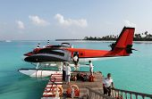 Red seaplane at the docks of an exotic resort in Maldives.