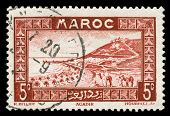 vintage stamp from Morocco depicting a traditional scenic view with camel riders