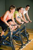Drei Personen In einem Fitnessstudio oder Fitness-Club, gekleidet In bunten Kleidern Radfahren; Konzentrieren sich auf die Reife Woma