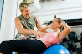 Woman doing sit-ups on a blue fitness ball in the gym, assisted by her personal trainer