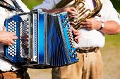 Bavarian traditional band with accordion and tuba playing marching music, only hands of musicians to