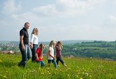 Happy family with Children walking down a meadow with dandelion flowers at a bright spring day, in the background a village is to be seen