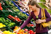 picture of supermarket  - woman in a supermarket at the vegetable shelf shopping for groceries - JPG