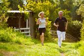 Mature or senior couple doing sport outdoors, jogging down a path in summer, the sun is low on eveni