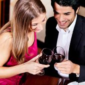 Young couple - man and woman - in a restaurant drinking glasses of red wine
