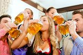 Inn or pub in Bavaria - group of five young men and women in traditional Tracht drinking beer and ha