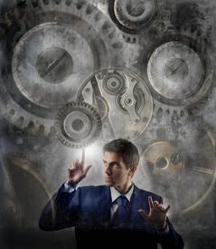 picture of mechanical engineer  - business man moving gear of big mechanism - JPG