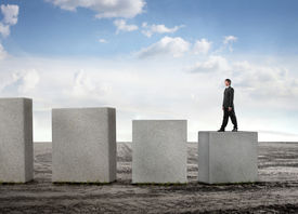 stock photo of step-up  - Businessman stepping up some cubes - JPG