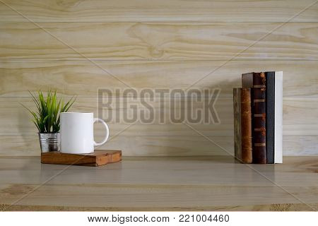 poster of Mockup background, books and coffee mug on wood desk and wooden wall with copy space.