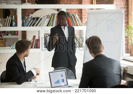 poster of African american businessman giving presentation to partners working with flip chart at corporate meeting, black business coach explaining project strategy using whiteboard on group office training