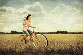 foto of riding-crop  - a pretty girl riding her bike in a field full of yellow flowers - JPG
