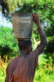 foto of peddlers  - an African woman transports a bucket of water on the head - JPG